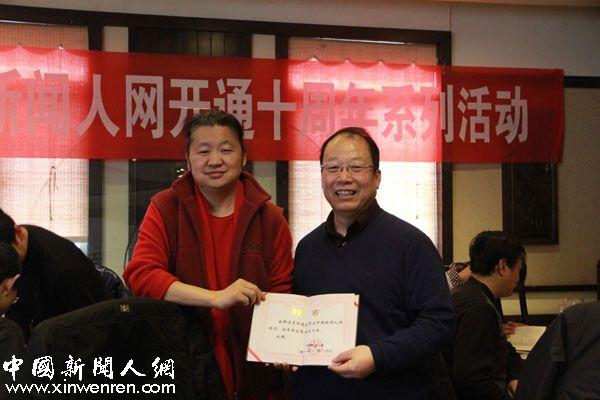 著名书画家、陕西唐人书画院院长孙光(左)为西安交大新闻与传播研究所所长李明德(右)颁发中国新闻人网顾问聘书