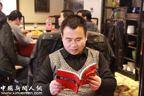 《人民政协报》记者顾宸宇在欣赏纪念册