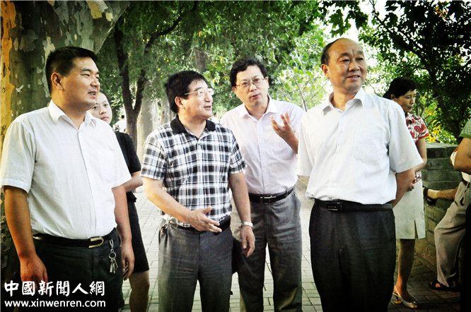 中共滁州市委副秘书长、滁州市人民政府信访局局长谭启源(右)在清流河旁与企业家日报社中国企业家联盟副主席周纪发等人交流